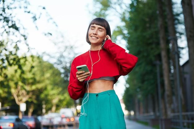 Bella donna emotiva ascoltando musica per strada, donna millenaria carina in maglione rosso elegante utilizzando erphones sul moderno