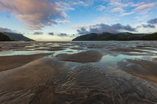 Bella spiaggia deserta con nuvole drammatiche e increspature della marea che escono nella sabbia.