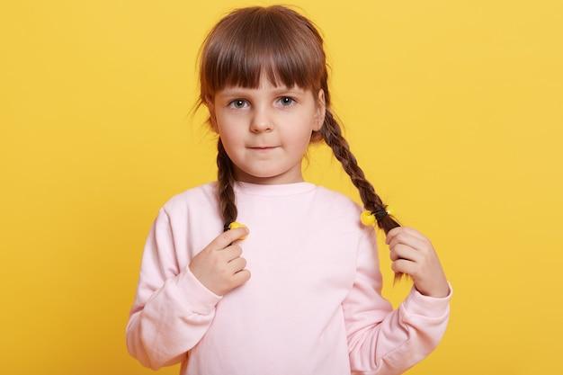 Bella femmina europea che indossa abbigliamento casual in posa con le labbra increspate e guardando direttamente la fotocamera su giallo