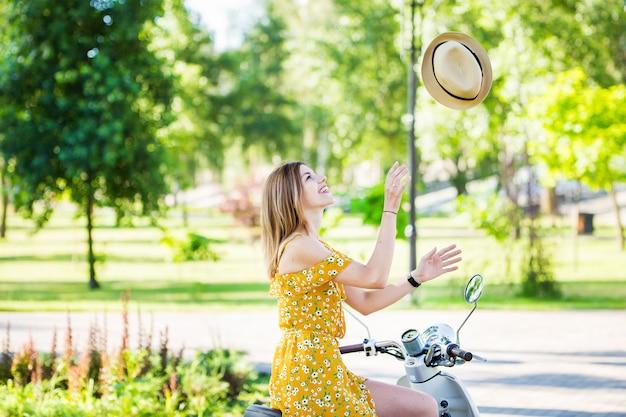 Bella ragazza europea in un vestito giallo con uno scooter retrò nel parco mattina
