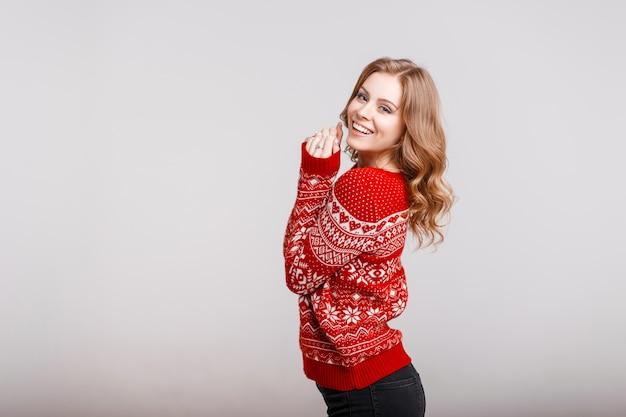 Modello di bella donna europea in un maglione rosso alla moda con una stampa in studio