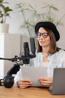 Il podcaster di bella donna europea con cuffie e microfono registra podcast in registrazione