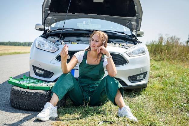 La bella donna europea ripara l'auto sulla strada
