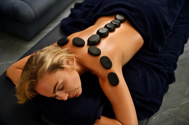 Bella giovane donna bionda europea con un bel viso sdraiato su un lettino da massaggio con pietre laviche calde sulla schiena lungo la colonna vertebrale che riceve un trattamento ayurvedico in una clinica spa benessere