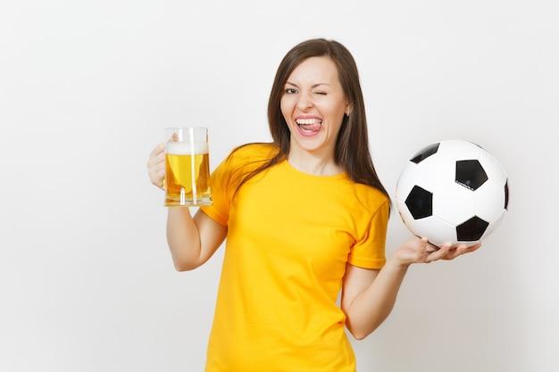 Bella giovane donna allegra europea, tifoso o giocatore in uniforme gialla che tiene boccale di birra, pallone da calcio isolato su priorità bassa bianca. sport, giocare a calcio, concetto di stile di vita sano.