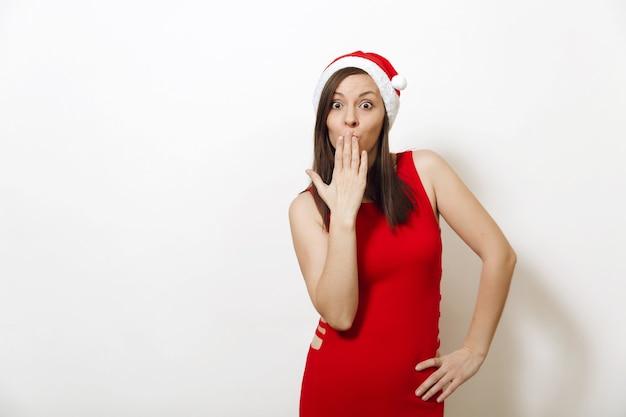 La bellissima giovane donna europea felice con un sorriso affascinante che indossa un abito rosso e un cappello di natale che si copre la bocca con la mano su sfondo bianco. ragazza di santa isolata. concetto di festa di capodanno 2018