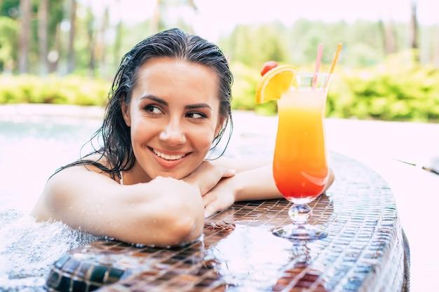 La bella donna sorridente eccitata si sta rilassando nella piscina estiva e beve un cocktail rinfrescante.