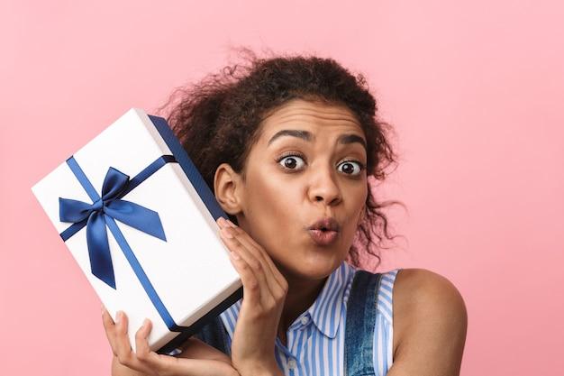 Bella giovane donna africana emozionante che tiene il contenitore di regalo sopra il rosa