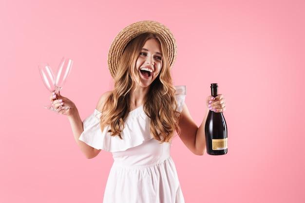Bella ragazza bionda eccitata che indossa un abito estivo in piedi isolato su un muro rosa, festeggia con una bottiglia di champagne e due bicchieri
