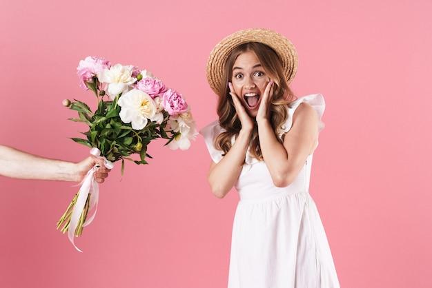 Bella giovane ragazza bionda eccitata che indossa un abito estivo in piedi isolato su un muro rosa, ricevendo un mazzo di peonie come regalo