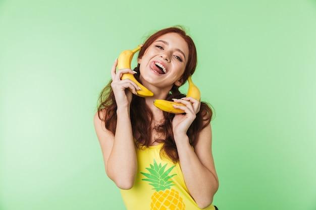 Bella eccitato giovane ragazza rossa in posa isolato su parete verde sfondo con frutti di banane immaginare chiamata di telefonia mobile parlando.