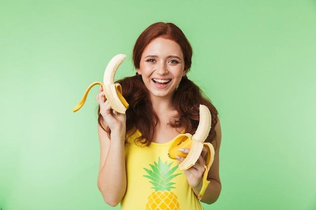 Bella giovane ragazza rossa eccitata in posa isolata su sfondo verde muro con frutti di banane.