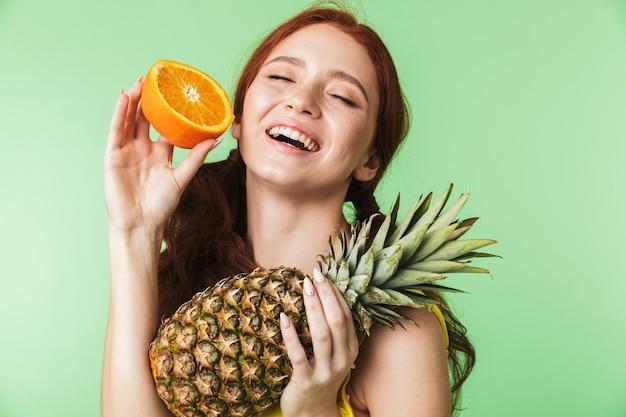 Bella eccitato giovane ragazza rossa in posa isolato su parete verde sfondo con agrumi vitamine e ananas.