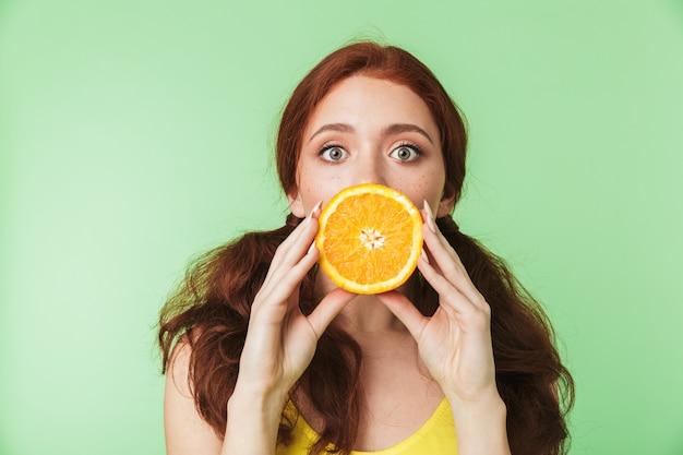 Bella eccitato giovane ragazza rossa in posa isolato su parete verde sfondo con agrumi vitamine frutti.