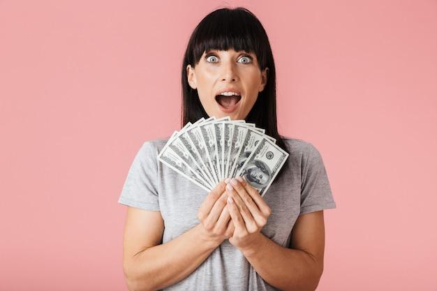Una bella giovane donna eccitata in posa isolata sul muro rosa che tiene i soldi.