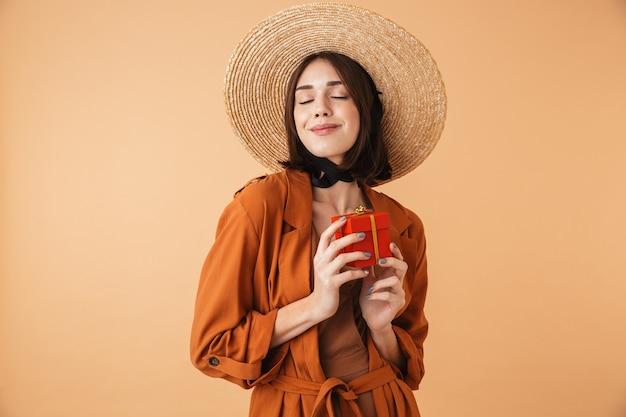 Bella giovane donna eccitata che indossa un cappello di paglia e un vestito estivo in piedi isolato su un muro beige, con in mano una scatola regalo