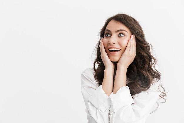 Bella giovane donna eccitata con lunghi capelli castani ricci che indossa una camicia bianca in piedi isolata sul muro bianco, distogliendo lo sguardo