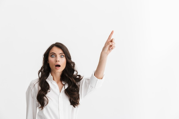 Bella giovane donna eccitata con lunghi capelli castani ricci che indossa una camicia bianca in piedi isolata sul muro bianco, puntando il dito sullo spazio della copia