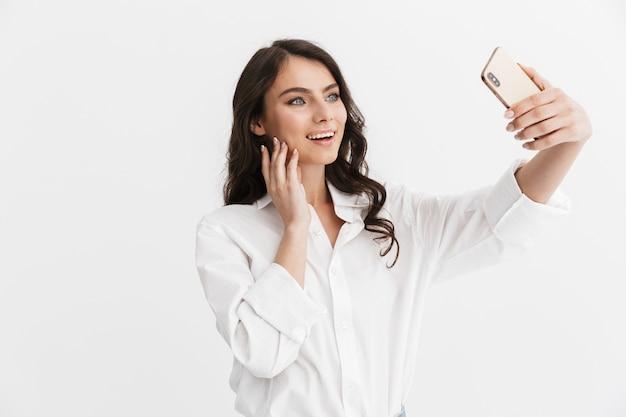 Bella giovane donna eccitata con lunghi capelli castani ricci che indossa una camicia bianca in piedi isolata sul muro bianco, facendo un selfie