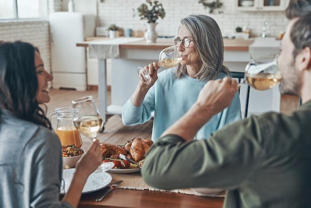 Bella famiglia che beve vino e sorride mentre cena insieme