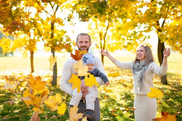 Bella famiglia divertendosi con il loro bambino nel parco di autunno.