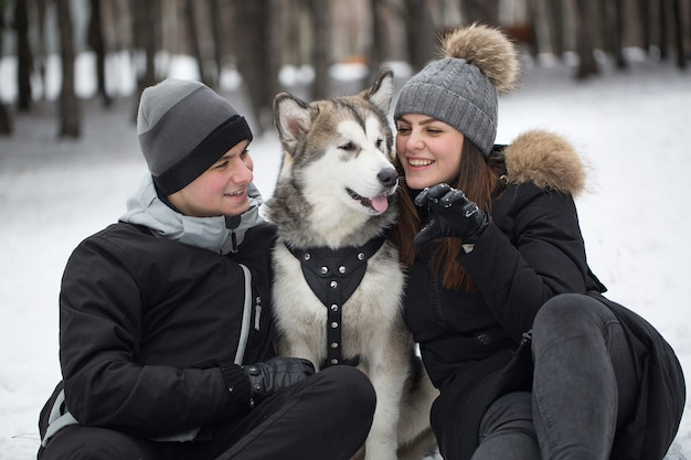 Bella famiglia, un uomo e una ragazza nella foresta invernale con il cane. gioca con il cane siberian husky.