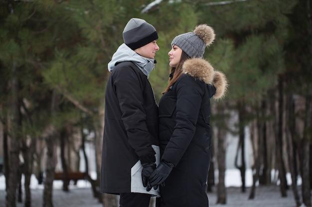 Bella famiglia, uomo e donna nel bosco in inverno