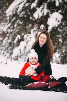 Bella famiglia della madre e la sua piccola figlia che godono del giorno di inverno nevoso in foresta