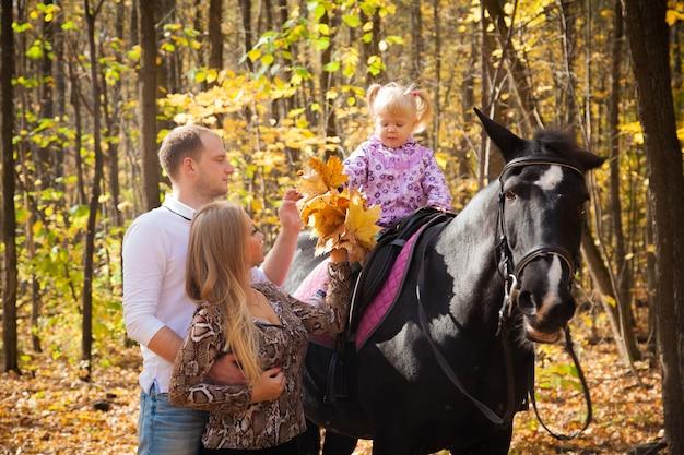 Bella famiglia in una passeggiata con un cavallo nella foresta autunnale mamma papà e figlia