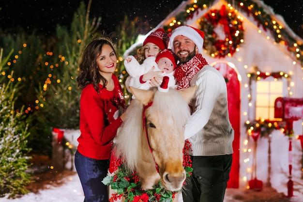 Bella famiglia con bambini e pony a natale