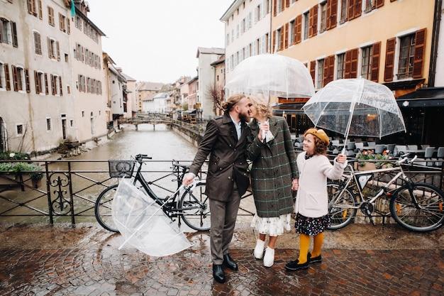 Bella famiglia con ombrelloni in caso di pioggia ad annecy. francia.famiglia a piedi sotto la pioggia.
