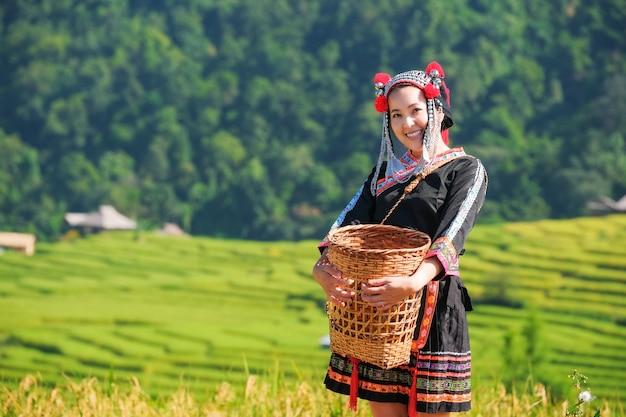 Una bella ragazza contadina con paglia nelle risaie nel nord della thailandia