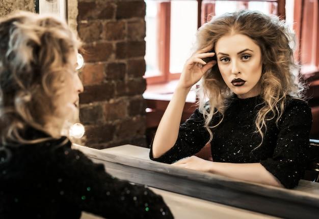 Bella donna bionda di moda in posa vicino allo specchio