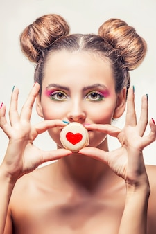 La bella ragazza del modello di modo con i biscotti dolci con i cuori su una superficie bianca ama il giorno di san valentino