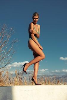 Bellissima modella in costume da bagno in posa su uno sfondo di cielo.