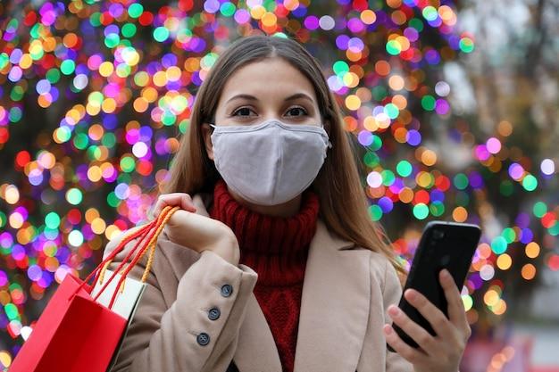 Bella donna di moda con maschera facciale e borse della spesa che acquistano online con smart phone in strada con le luci dell'albero di natale