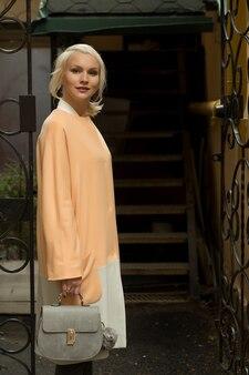 Bella donna bionda alla moda sulla strada della città. estate.