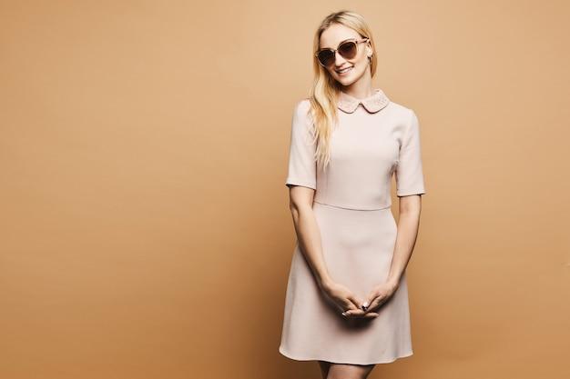Ragazza bionda bellissima e alla moda con un corpo perfetto in elegante abito corto beige e occhiali da sole alla moda, sorridente e in posa
