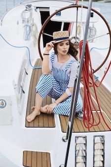 Bella e alla moda modella bruna ragazza in eleganti tute a strisce bianche e blu e con un cappello, tiene il suo cappello alla moda, si siede e posa su una nave yacht al mare