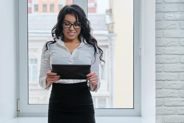 Bella donna d'affari alla moda con tavoletta digitale