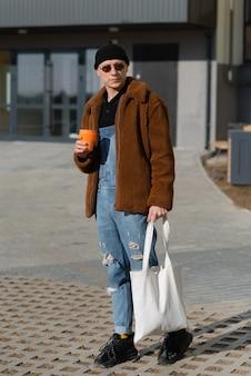 Bellissimo uomo alla moda con borsa e tazza di caffè per strada