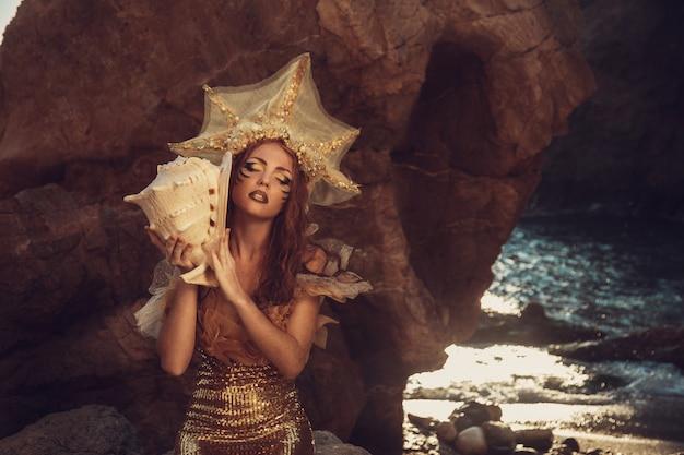 Bella sirena alla moda che si siede su una roccia in riva al mare
