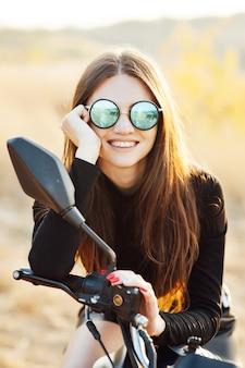 Bella donna alla moda su una moto classica, aspetto modello con occhiali da sole.