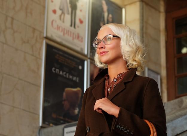 Bella donna alla moda in piedi sulla strada della città. giornata d'autunno. Foto Premium
