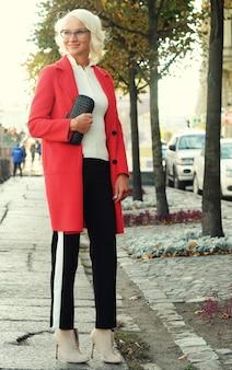 Bella donna alla moda in piedi sulla strada della città. giornata d'autunno.