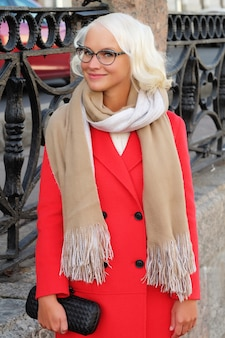 Bella donna alla moda in piedi sulla strada della città. giorno d'autunno.