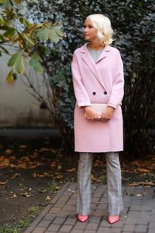 Bella donna alla moda in piedi sulla strada della città