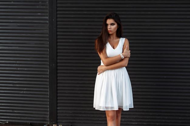 Bella donna alla moda in un abito bianco vicino a rotoli di metallo