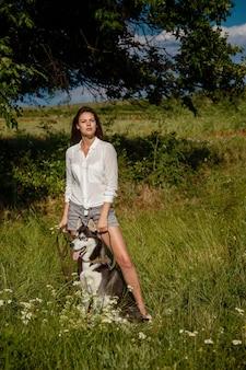 Bella giovane donna alla moda in pantaloncini di jeans e una camicetta bianca in posa nel parco con un husky
