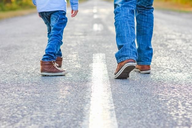 A bei piedi di genitore e bambino sulla strada nel parco in viaggio nella natura